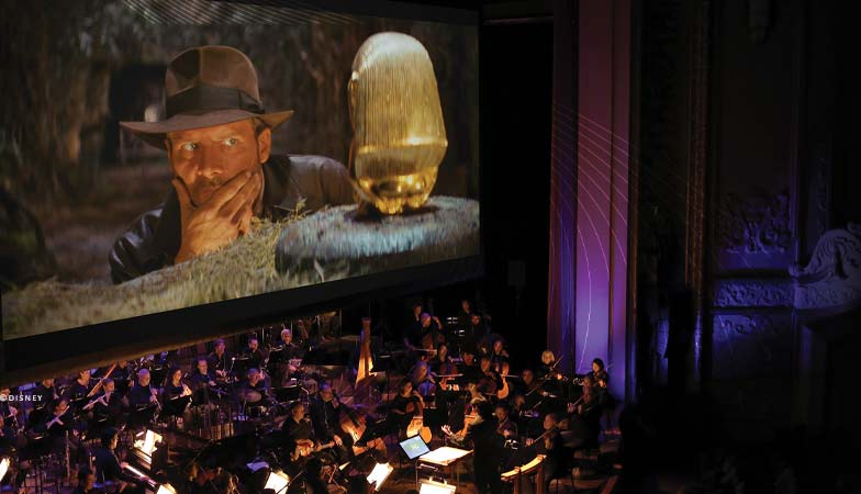 The orchestra performs with a film screen behind them