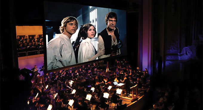 A movie projected above the orchestra