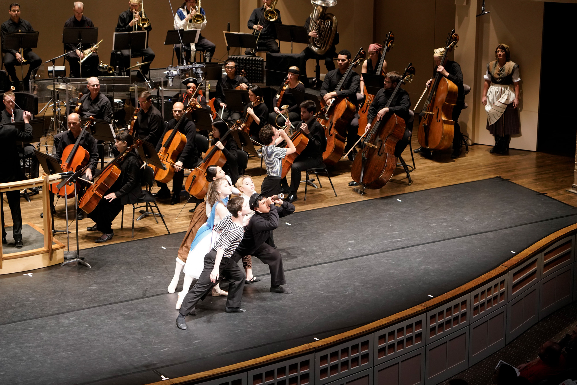 Dancers appear in front of the orchestra
