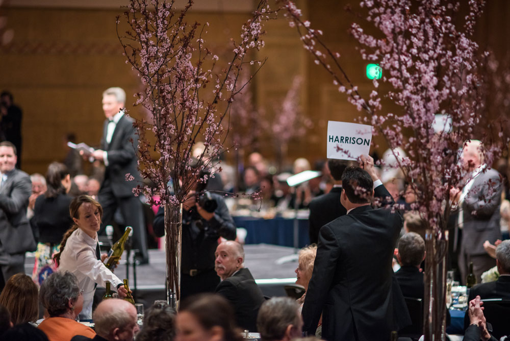 A person raising a sign at the gala