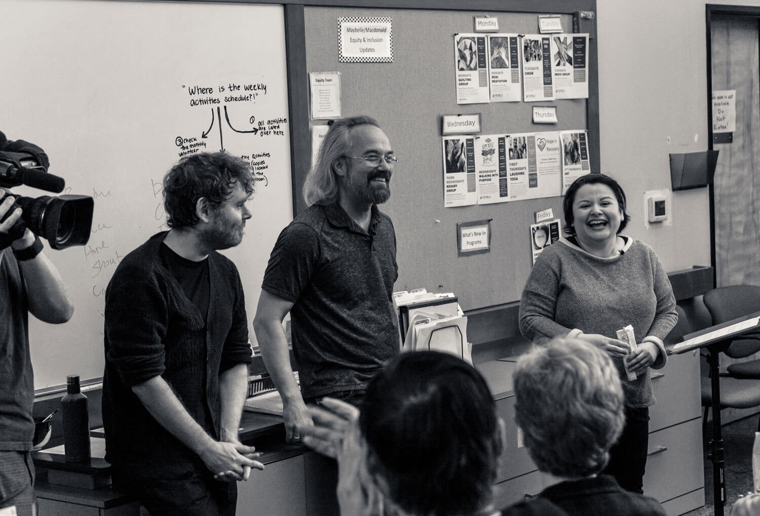 Carlos Kalmar and Gabriel Kahane discuss emergency shelter intake form with the choir